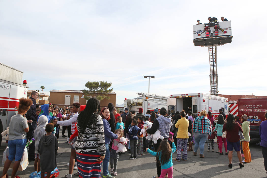 Families socialize and children receive gifts at the Desert Palms Apartments, Sunday, Dec. 24, 2017, in North Las Vegas. North Las Vegas Fire Department emergency vehicles arrived with sirens blaz ...