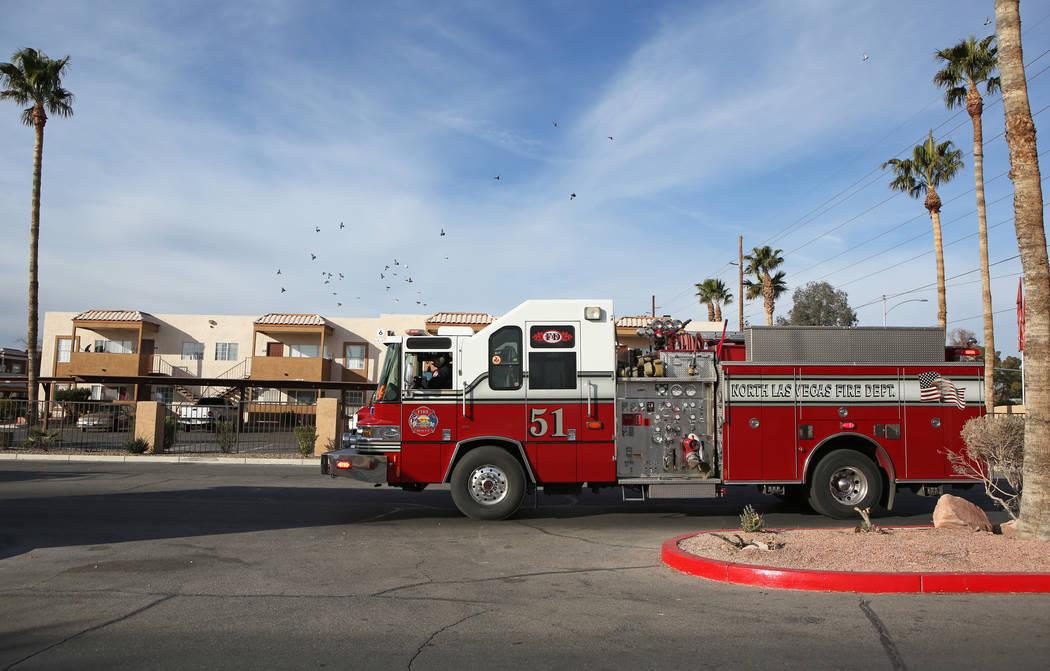 North Las Vegas Fire Department emergency vehicles arrive with sirens blazing at Desert Palms Apartments to surprise families with toys on Sunday, Dec. 24, 2017, in North Las Vegas. Ronda Churchil ...