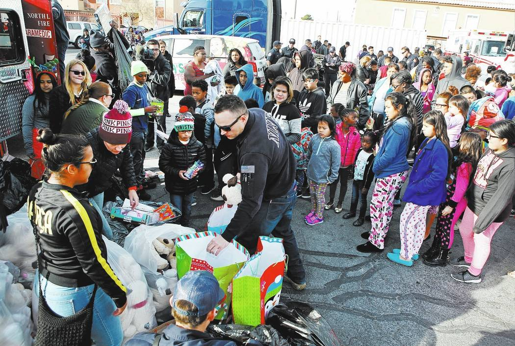 Families wait in line to receive gifts from North Las Vegas Fire Department at the Desert Palms Apartments, Sunday, Dec. 24, 2017, in North Las Vegas. Fire department emergency vehicles arrived wi ...