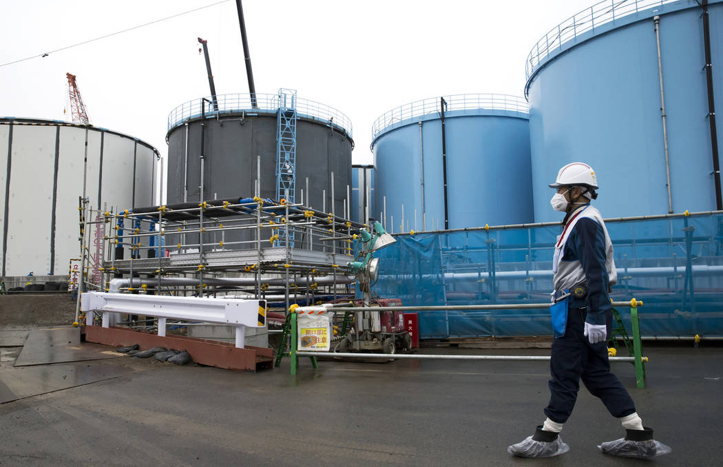 FILE - In this Feb. 23, 2017, file photo, an employee walks past storage tanks for contaminated water at the tsunami-crippled Fukushima Dai-ichi nuclear power plant of the Tokyo Electric Power Co. ...