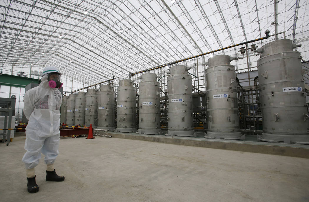 FILE - In this Nov. 12, 2014 file photo, a Tokyo Electric Power Co. (TEPCO) official wearing a radioactive protective gear stands in front of Advanced Liquid Processing Systems during a press tour ...