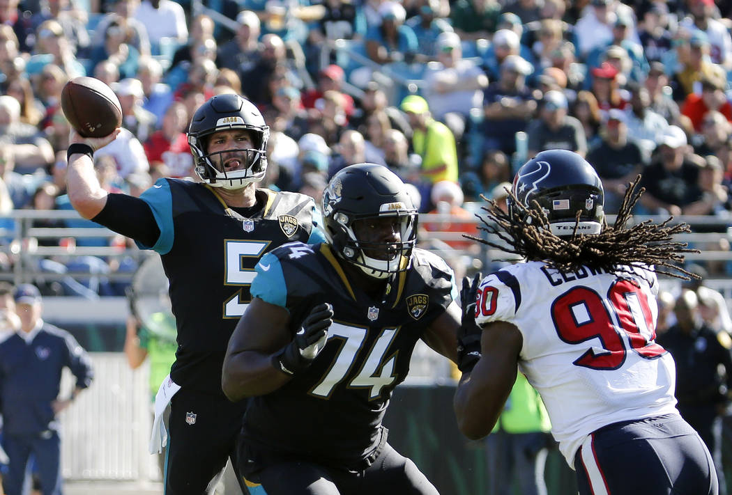 Jacksonville Jaguars quarterback Blake Bortles (5) throws a pass as offensive lineman Cam Robinson (74) blocks Houston Texans defensive end Jadeveon Clowney (90) during the first half of an NFL fo ...