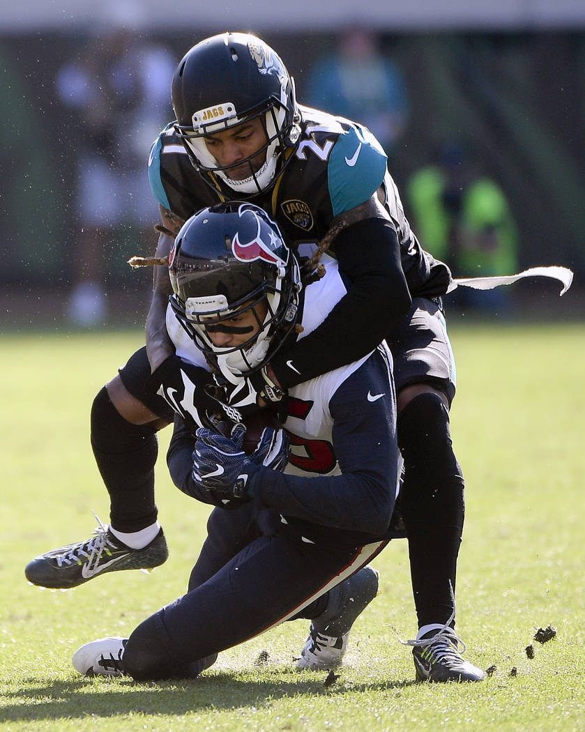 Houston Texans wide receiver Will Fuller V, bottom, is stopped by Jacksonville Jaguars cornerback A.J. Bouye (21) after a reception during the first half of an NFL football game, Sunday, Dec. 17,  ...