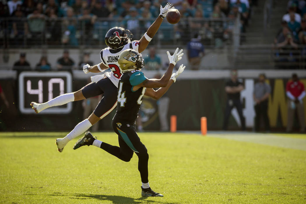 Jacksonville Jaguars wide receiver Keelan Cole (84) makes a catch for a 32-yard gain in front of Houston Texans cornerback Kevin Johnson during the first half of an NFL football game, Sunday, Dec. ...