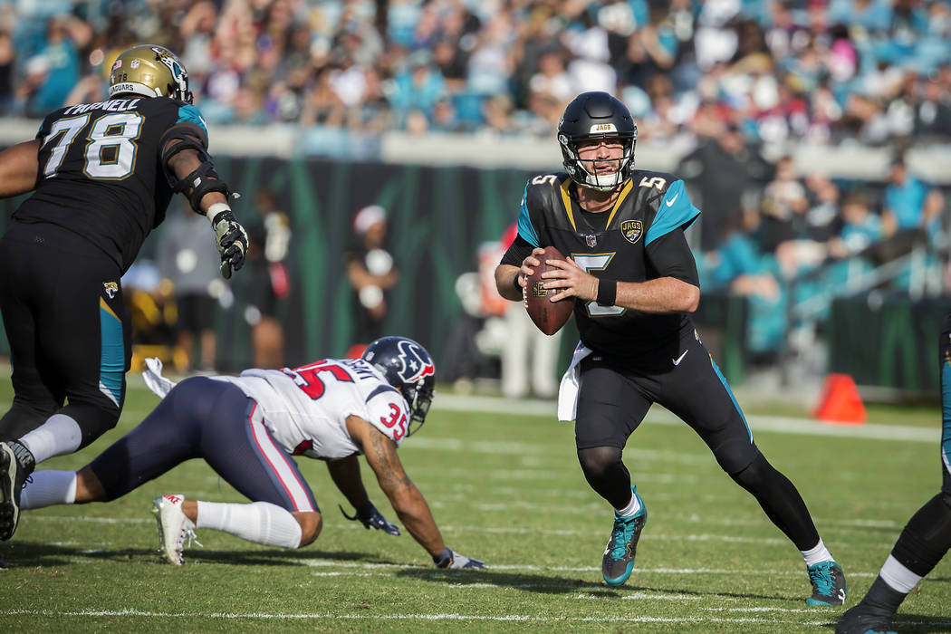 Jacksonville Jaguars quarterback Blake Bortles (5) looks down field as he scrambles against the Houston Texans during the first half of an NFL football game, Sunday, Dec. 17, 2017, in Jacksonville ...