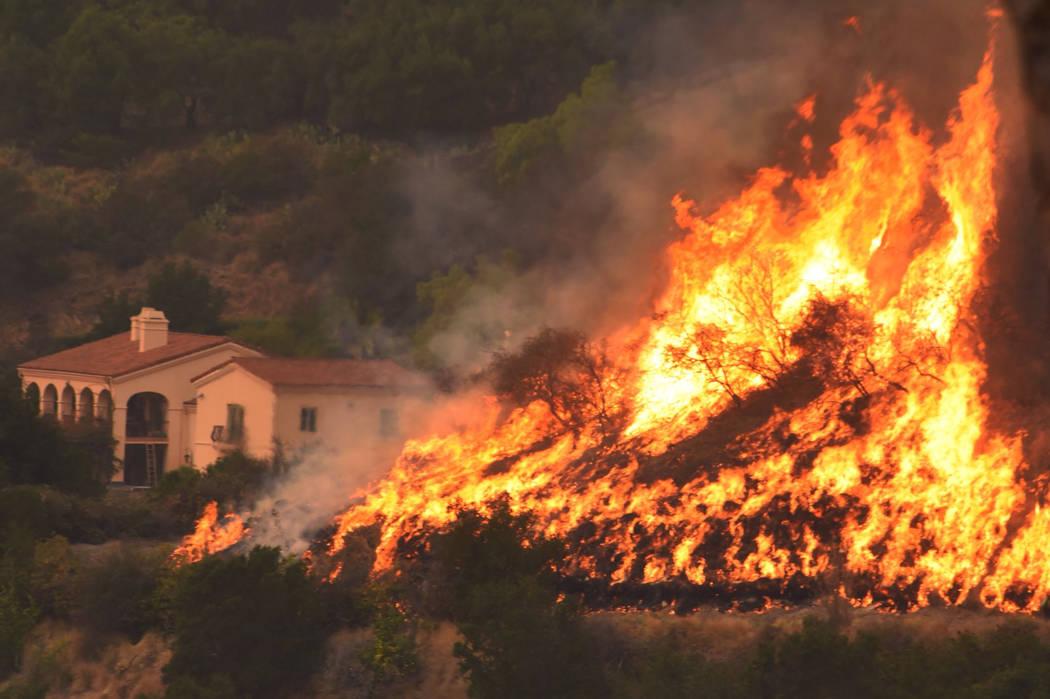 Flames from a back firing operation underway rise behind a home off Ladera Lane near Bella Vista Drive in Santa Barbara, Calif. on Thursday, Dec. 14, 2017. (Mike Eliason/Santa Barbara County Fire  ...