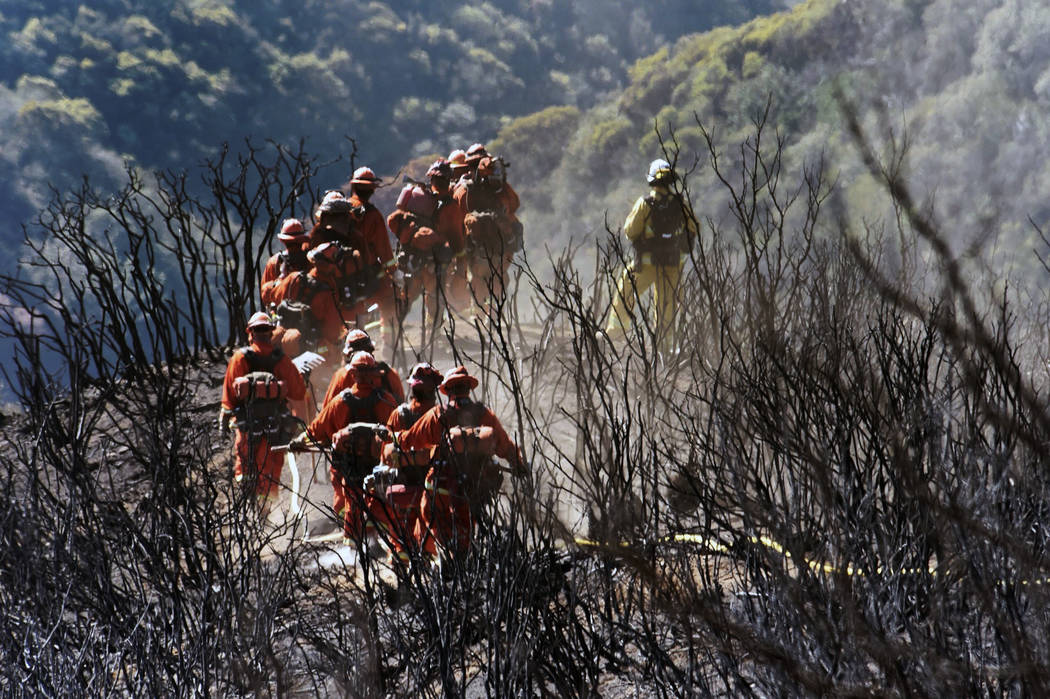 In this photo provided by the Santa Barbara County Fire Department, CAL FIRE Inmate Firefighting Hand Crew members hike through the charred landscape on their way to work east of Gibraltar Road ab ...