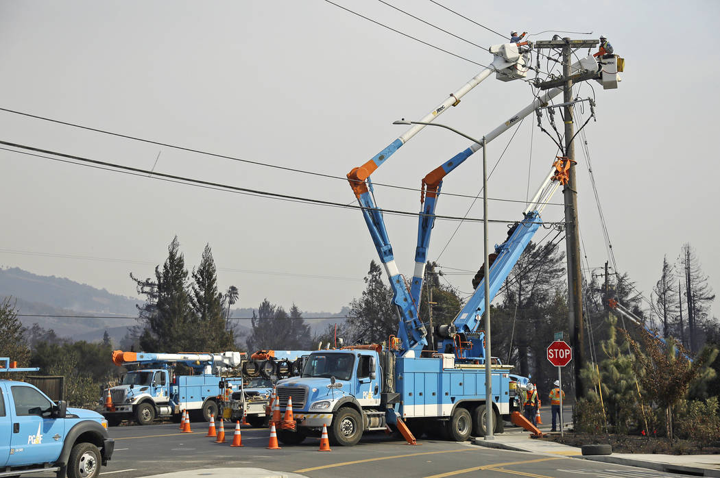 A Pacific Gas & Electric crew works at restoring power along the Old Redwood Highway in Santa Rosa, Calif. on Oct. 11, 2017. California utility Pacific Gas & Electric Co. is suspending div ...