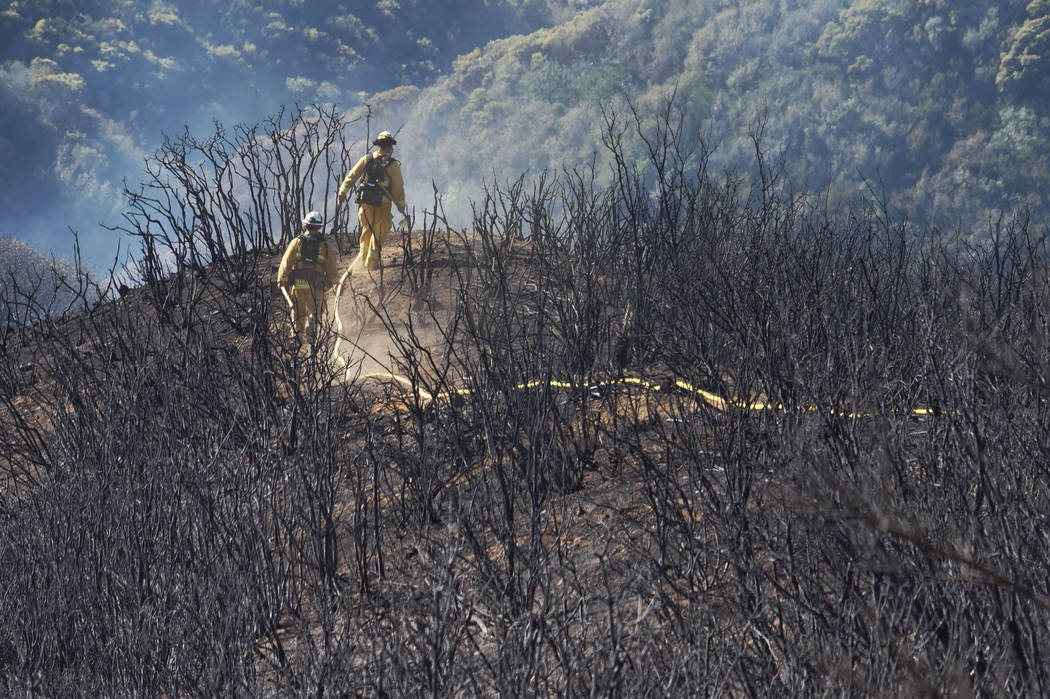 In this photo provided by the Santa Barbara County Fire Department, firefighters follow a hose line while walking rugged and scorched terrain below E. Camino Cielo near Gibraltar Road in Santa Bar ...
