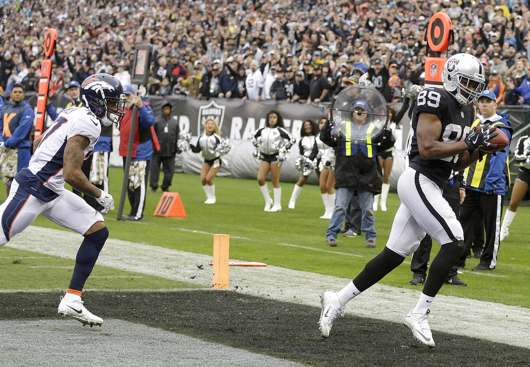 Oakland Raiders wide receiver Amari Cooper (89) catches a touchdown pass in front of Denver Broncos cornerback Brendan Langley (27) during the first half of an NFL football game in Oakland, Calif. ...