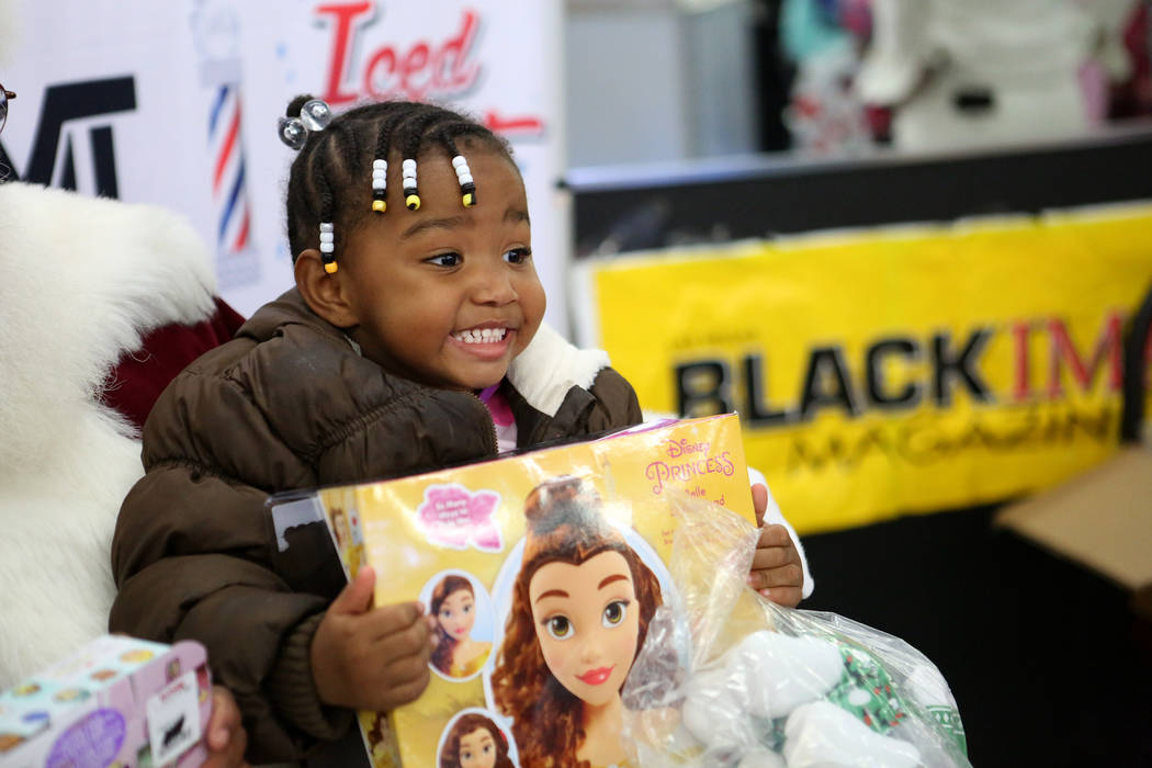 Jewel Lofton, 3, shows off her new toy from Santa's lap at the Mayweather toy giveaway at Iced Out Barber Shop Las Vegas on Friday, Dec. 22, 2017. Michael Quine Las Vegas Review-Journal @Vegas88s