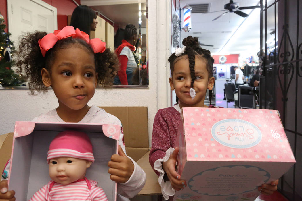 Kylia, 4, left, and sister Kayln Braggs, 3, pick up their presents at the Mayweather toy giveaway at Iced Out Barber Shop Las Vegas on Friday, Dec. 22, 2017. Michael Quine Las Vegas Review-Journal ...