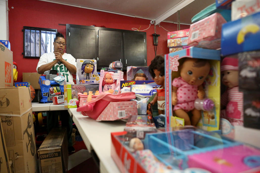Kimberly Mason surveys the bounty of toys that she and other volunteers will distribute at the Mayweather toy giveaway at Iced Out Barber Shop in Las Vegas on Friday, Dec. 22, 2017. Michael Quine  ...