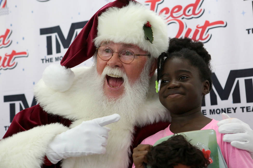 Yalaiyah Redford, 9, musters a smile for her picture with Charlie Bush as Santa at the Mayweather toy giveaway at Iced Out Barber Shop Las Vegas on Friday, Dec. 22, 2017. Michael Quine Las Vegas R ...