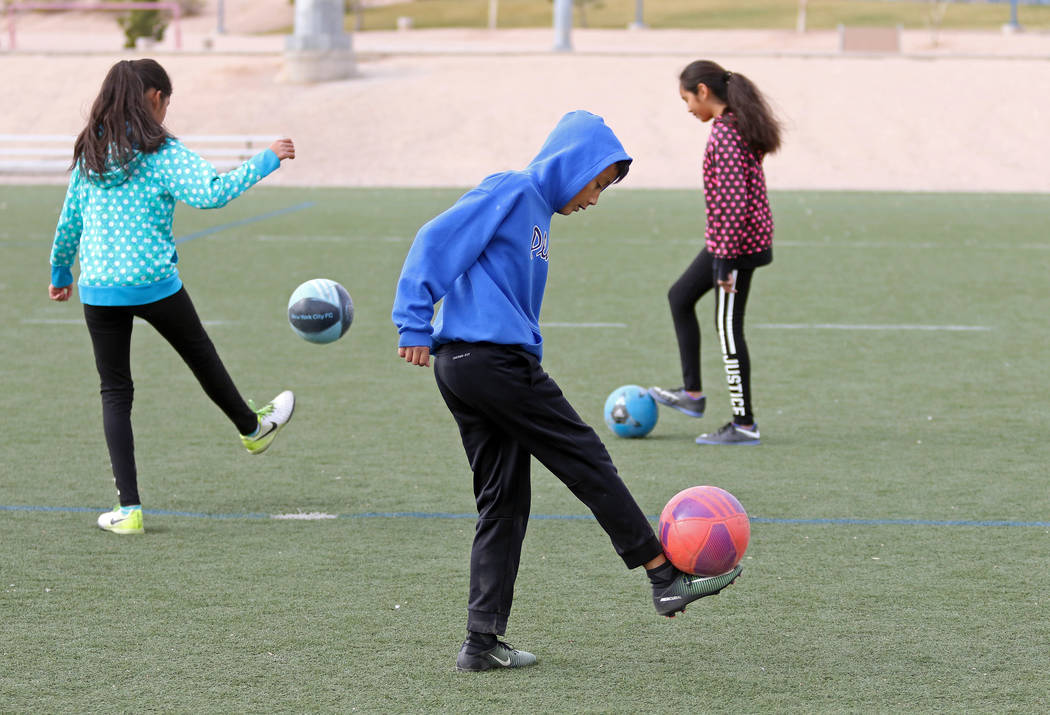 Brandon Alvarez, 9, front, practices soccer moves alongside his twin sisters Jazmin, 11, left, and Yunuen, 11, during a family soccer session at Kellogg Zaher Soccer Complex on Christmas Eve morni ...
