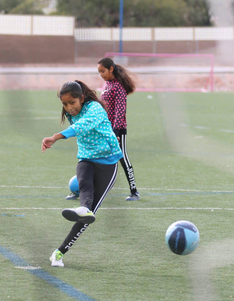 Jazmin Alvarez, 11, front, kicks for a goal near her twin sister Yunuen during a family soccer session at Kellogg Zaher Soccer Complex on Christmas Eve morning Sunday, Dec. 24, 2017, in Las Vegas. ...