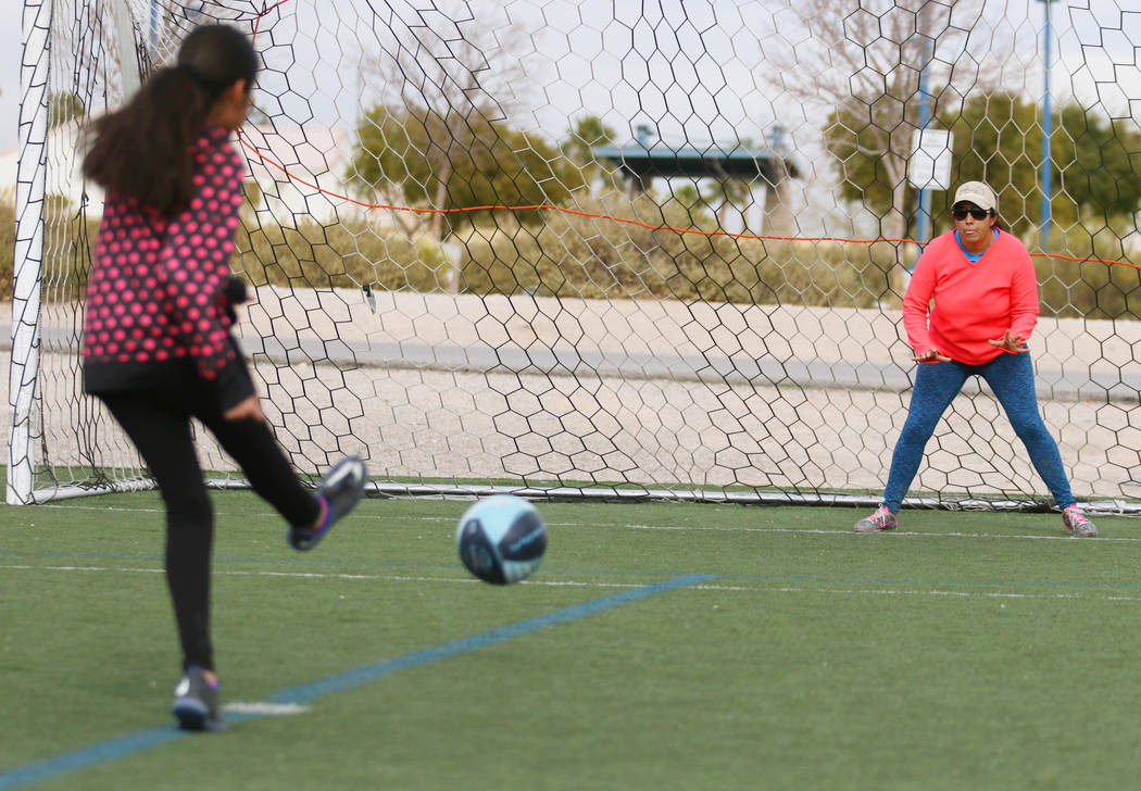Yunuen Alvarez, 11, kicks for a goal while her mother Maricruz waits to block during a family soccer session at Kellogg Zaher Soccer Complex on Christmas Eve morning Sunday, Dec. 24, 2017, in Las  ...