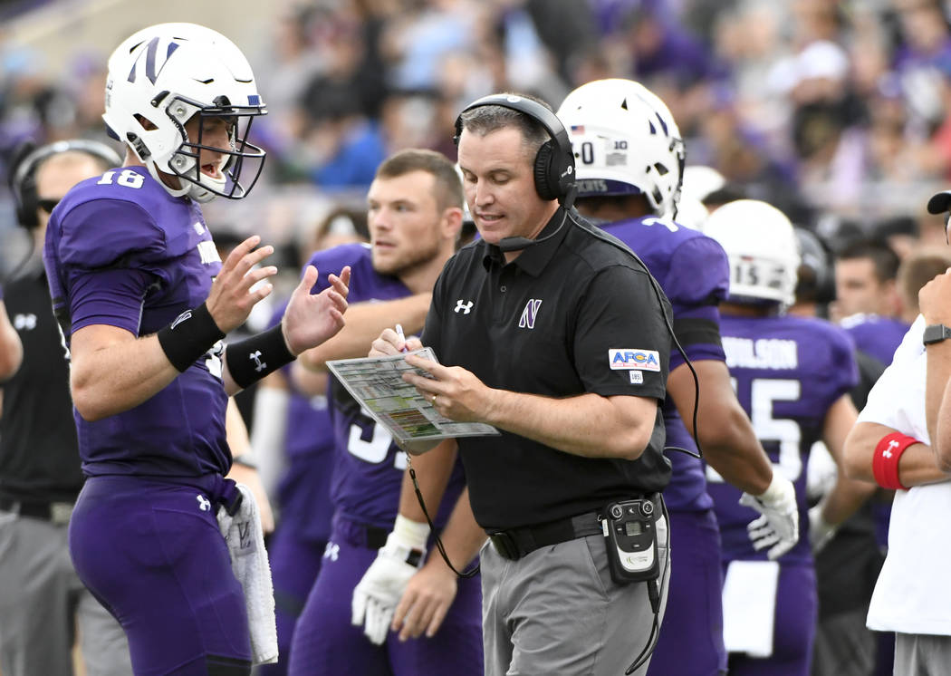 Northwestern Wildcats head coach Pat Fitzgerald talks with quarterback Clayton Thorson (18), left, after he threw an interception against Nevada during the second half of an NCAA college football  ...