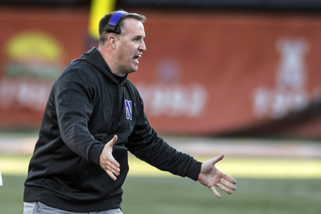 Northwestern head coach Pat Fitzgerald greets players after they come off the field during a break in play during the second quarter of an NCAA college football game against Illinois, Saturday, No ...