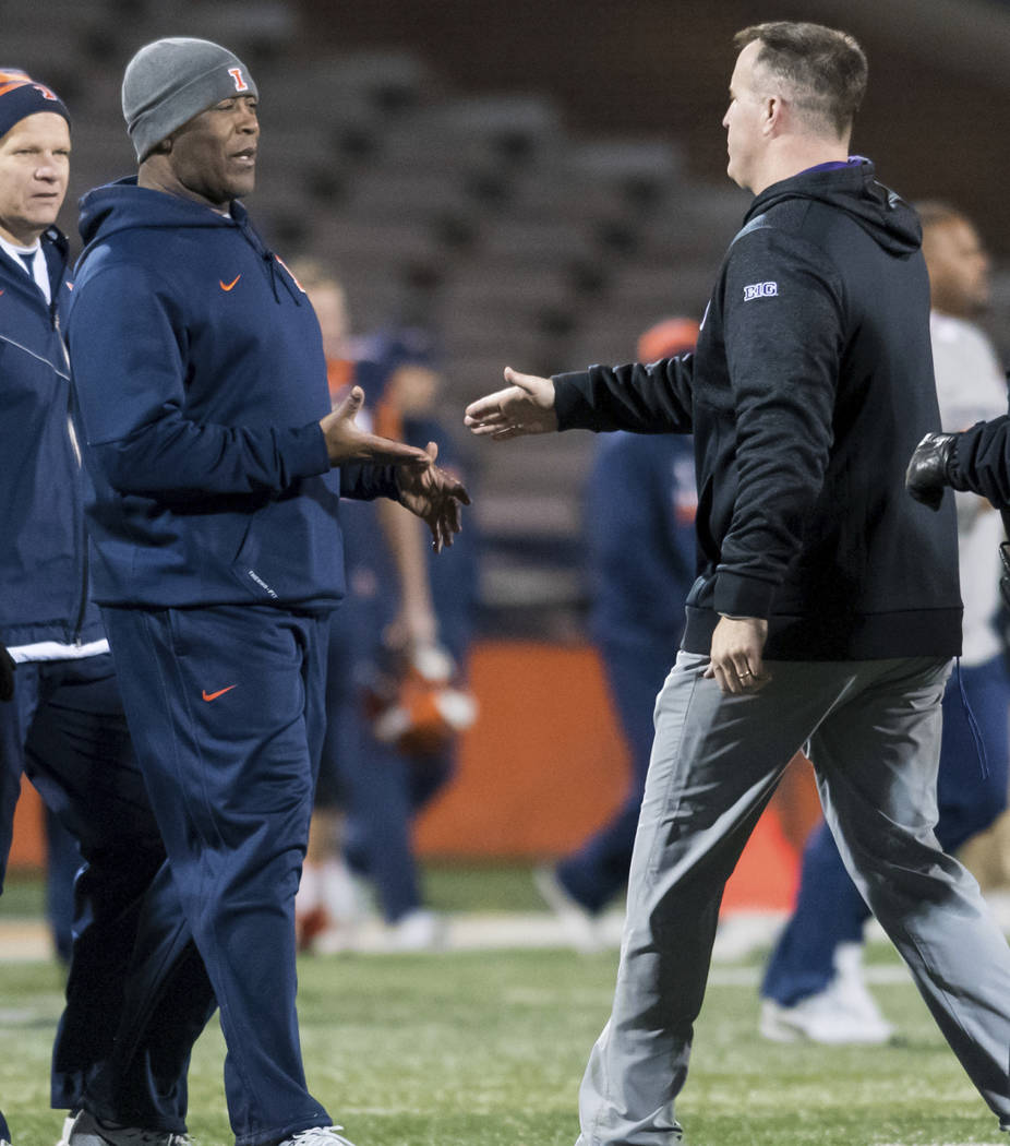 Illinois coach Lovie Smith, left, shakes hands with Northwestern coach Pat Fitzgerald after an NCAA college football game Saturday, Nov. 25, 2017, in Champaign, Ill. Northwestern defeated Illinois ...
