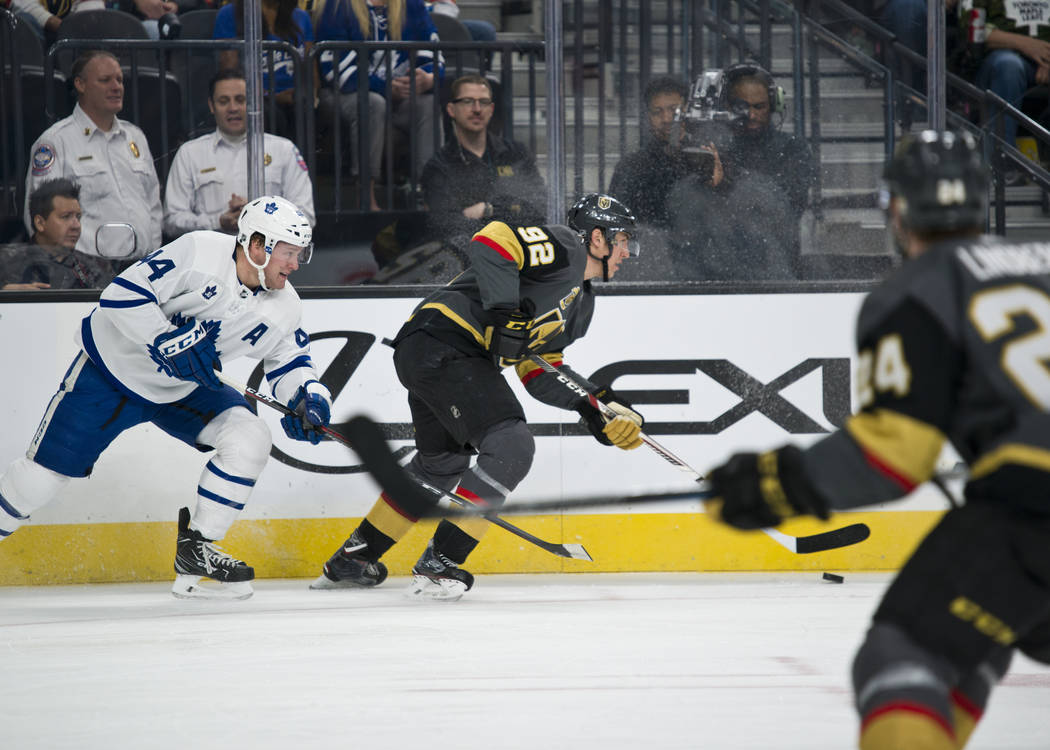 Vegas Golden Knights center Tomas Nosek (92) moves the buck by  Toronto Maple Leafs defenseman Morgan Rielly (44) during their game at T-Mobile Arena in Las Vegas on Sunday, December 31, 2017. Dan ...