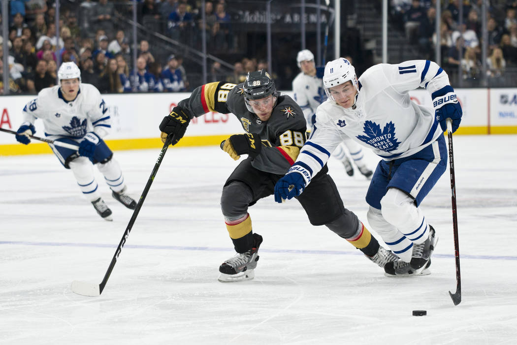 Vegas Golden Knights defenseman Nate Schmidt (88) races against Toronto Maple Leafs center Zach Hyman (11) fro the puck during their game at T-Mobile Arena in Las Vegas on Sunday, December 31, 201 ...
