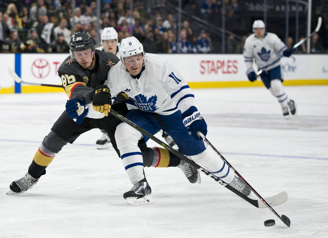 Vegas Golden Knights defenseman Nate Schmidt (88) struggles against Toronto Maple Leafs center Zach Hyman (11) fro the puck during their game at T-Mobile Arena in Las Vegas on Sunday, December 31, ...