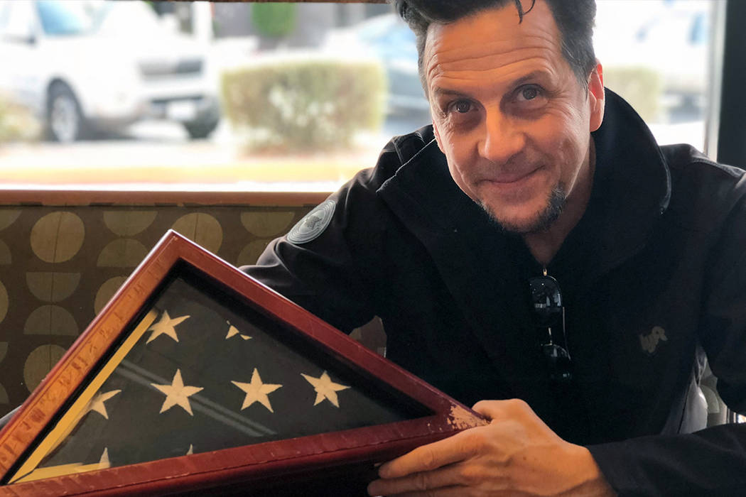 Joseph Mascolino is pictured with the burial flag he found on Thursday, Dec. 21 in the middle of the roadway near Buffalo Drive and Russell Road in the southwestern Las Vegas Valley. (Rio Lacanlal ...