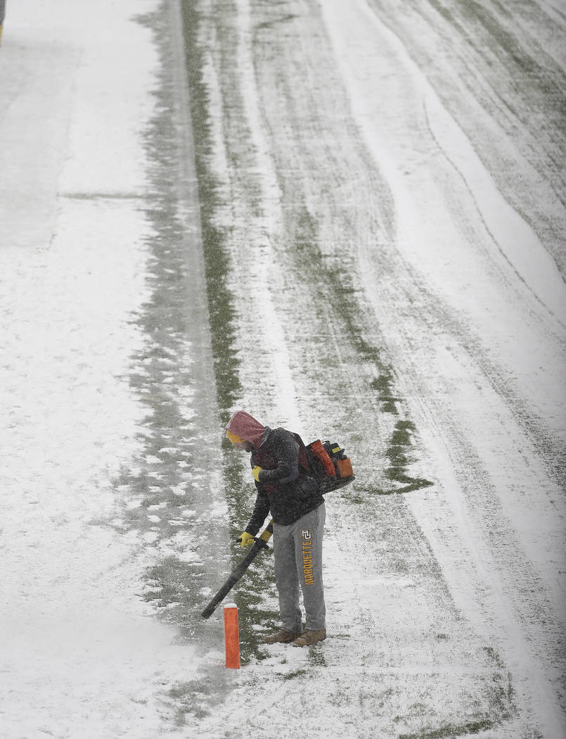 Workers clears snow from Soldier Field before an NFL football game between the Chicago Bears and Cleveland Browns in Chicago, Sunday, Dec. 24, 2017. (AP Photo/Charles Rex Arbogast)