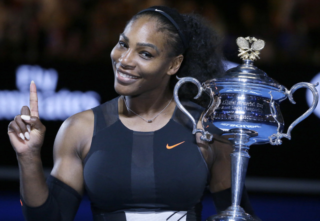 United States' Serena Williams holds up a finger and her trophy after defeating her sister ,Venus, in the women's singles final at the Australian Open tennis championships in Melbourne, Australia, ...