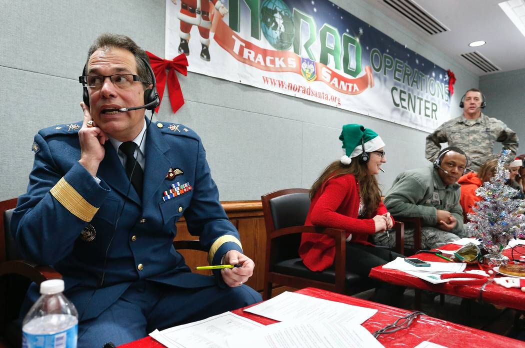 Canadian Brig. Gen. Guy Hamel, NORAD and USNORTHCOM Deputy Director of Policy, Strategy, and Plans, joins other volunteers taking phone calls from children around the world asking where Santa is a ...