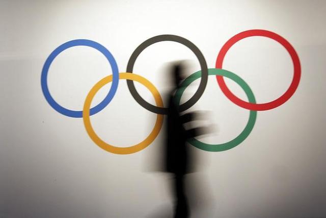 A man walks past the Olympic rings. (REUTERS/Eric Gaillard)