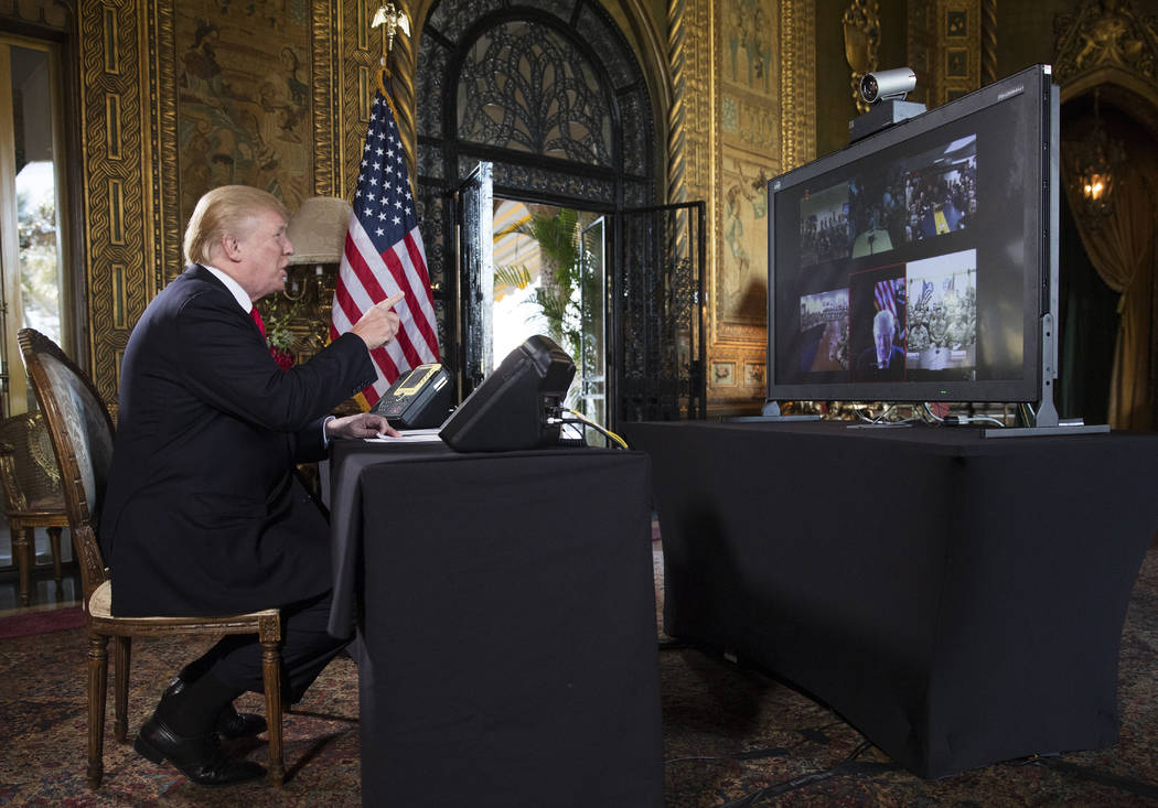 President Donald Trump points to the video screen during a Christmas Eve video teleconference with members of the mIlitary at his Mar-a-Lago estate in Palm Beach, Fla., Sunday, Dec. 24, 2017. (AP  ...