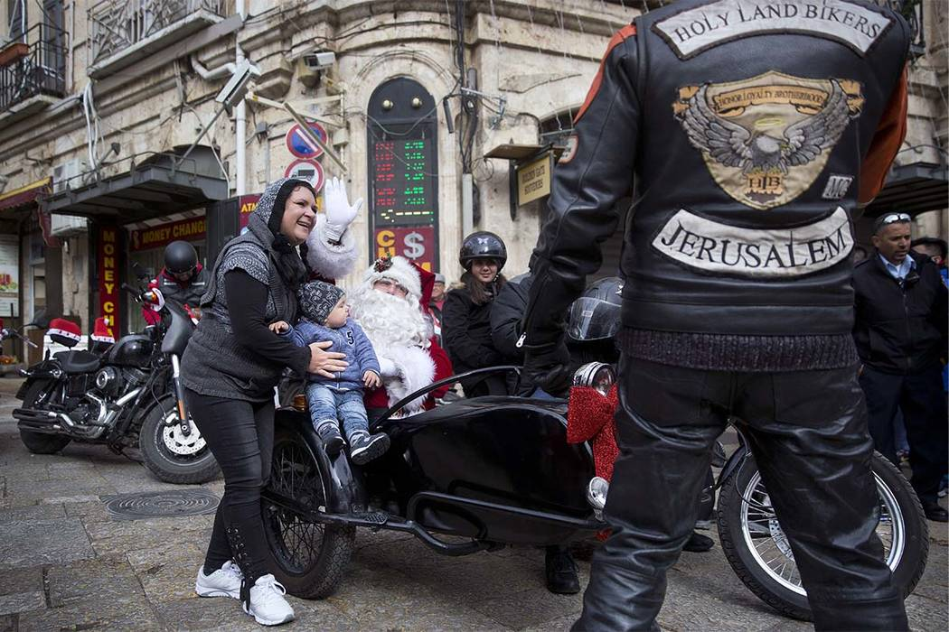 A man dressed as Santa Claus sits in a sidecar of a motorbike on Christmas Eve in Jerusalem Old City Sunday, Dec. 24, 2017. (AP Photo/Oded Balilty)