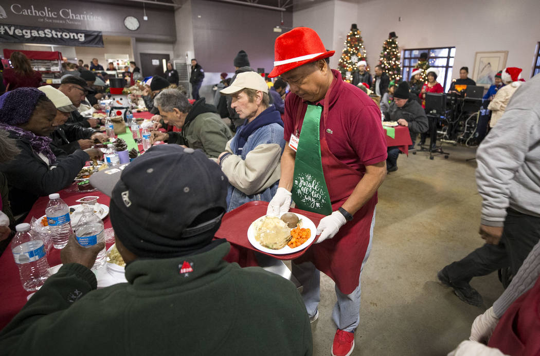 Las Vegas resident Amado Villegas delivers a Christmas dinner while volunteering at Catholic Charities' St. Vincent facility on Monday, Dec. 25, 2017, in Las Vegas. Richard Brian Las Vegas Review- ...