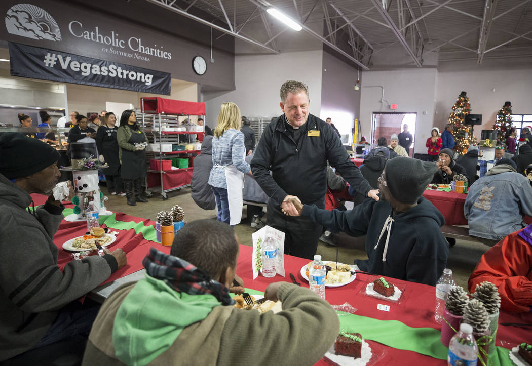 Catholic Charities of Southern Nevada President and CEO Deacon Thomas A. Roberts greets guests during Christmas dinner at Catholic Charities' St. Vincent facility on Monday, Dec. 25, 2017, in Las  ...