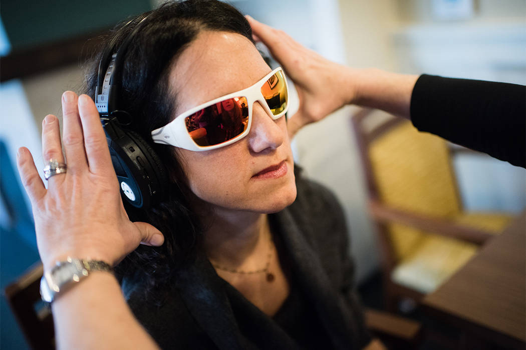 Washington Post reporter Tara Bahrampour wears glasses and headphones that limit her sight and hearing. (Sarah L. Voisin/The Washington Post)
