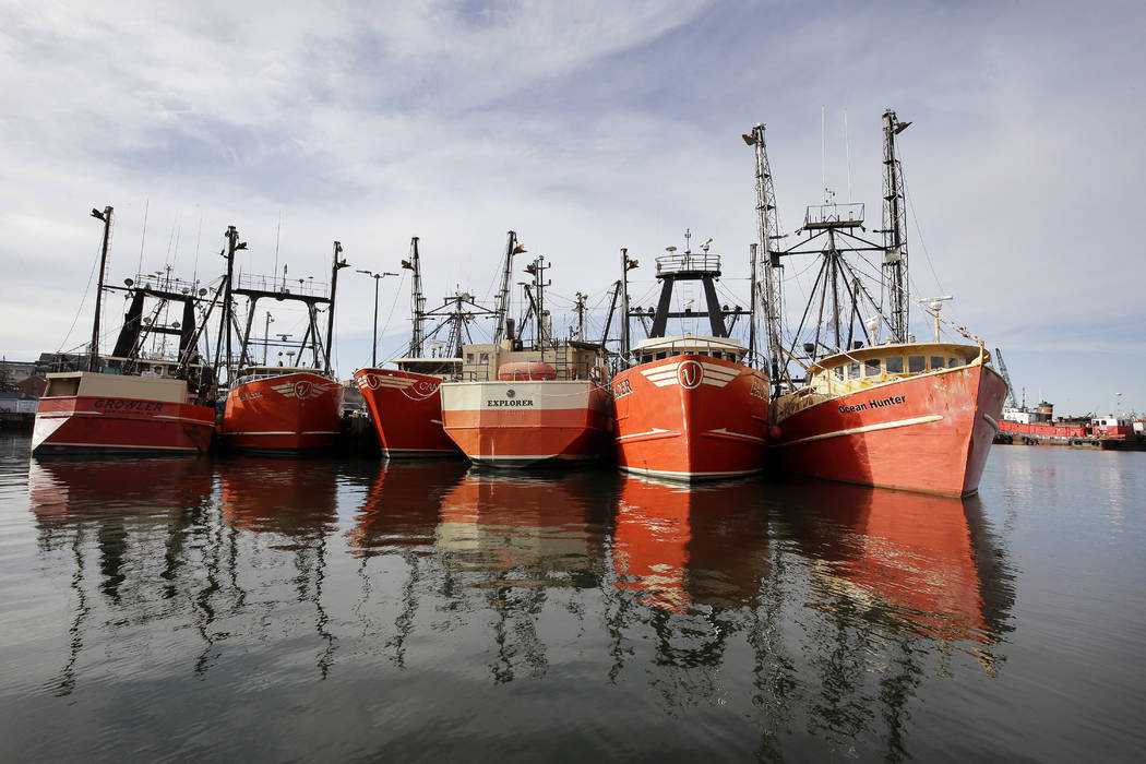 In this Wednesday, Dec. 6, 2017 photo fishing vessels are docked in New Bedford Harbor, in New Bedford, Mass. Fishermen in the nation's most lucrative port are turning a wary eye toward an emergin ...