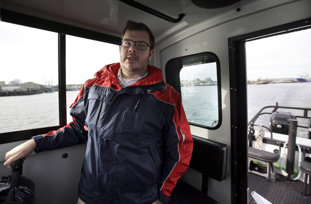 In this Wednesday, Dec. 6, 2017 photo Edward Anthes-Washburn, director of the Port of New Bedford, speaks with members of the media as he pilots a a vessel in the Acushnet River, off the coast of  ...
