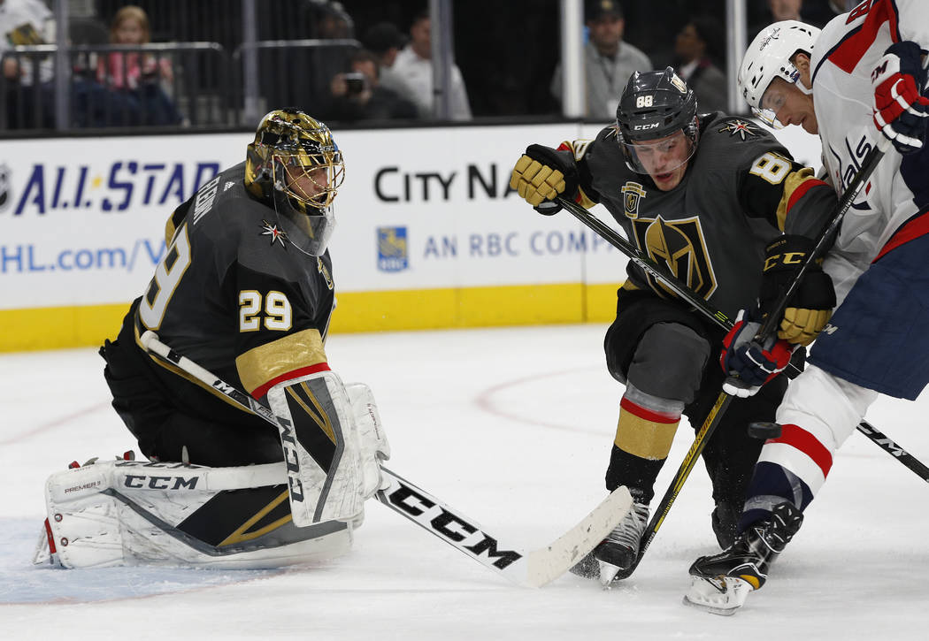Washington Capitals center Jay Beagle, right, and Vegas Golden Knights defenseman Nate Schmidt (88) vie for the puck after it was blocked by goalie Marc-Andre Fleury (29) during the second period  ...
