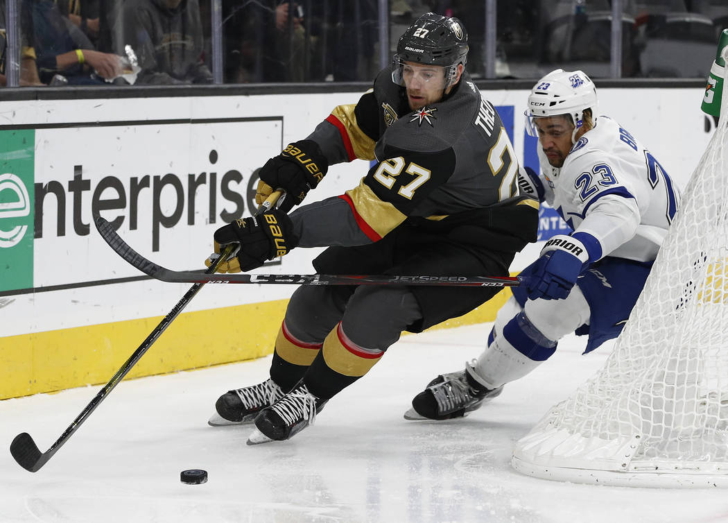 Vegas Golden Knights defenseman Shea Theodore, left, skates around Tampa Bay Lightning right wing J.T. Brown during the second period of an NHL hockey game Tuesday, Dec. 19, 2017, in Las Vegas. (A ...
