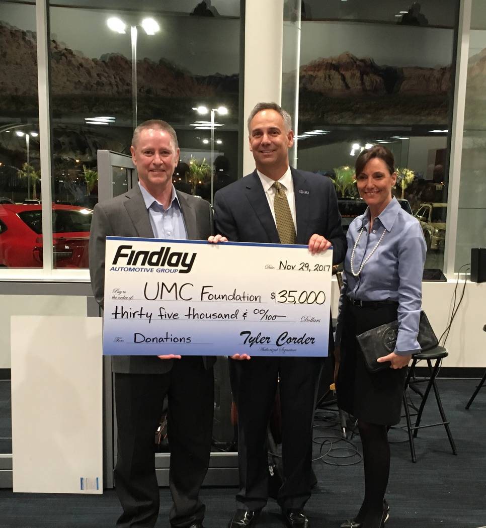 Findlay Automotive Findlay Automotive Group CFO Tyler Corder, left, presents a check for $35,000 to UMC CEO Mason Van Houweling and UMC chief administrative officer Marcia Turner.