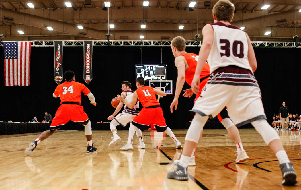 Carroll Pioneers' Ray Pierce (34) and teammate Ryan Clarey (11) guard Augsburg Auggies' Kevin McKiernan (11) during the first half of a basketball game in the D3Hoops.com Classic at the South Poin ...