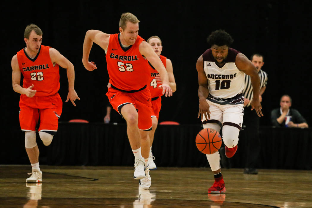 Carroll Pioneers' Tyler Ingebrigtsen (52) chases after Augsburg Auggies' Harry Sonie (10) during the first half of a basketball game in the D3Hoops.com Classic at the South Point Arena in Las Vega ...