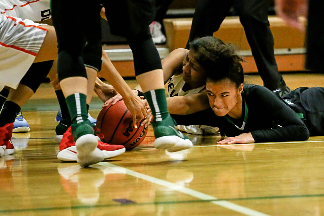 Green Valley's Rian Anderson (12), right, reaches for a loose ball during the second quarter of a basketball game against Beverly Hills during the Gator Winter Classic at Green Valley High School  ...