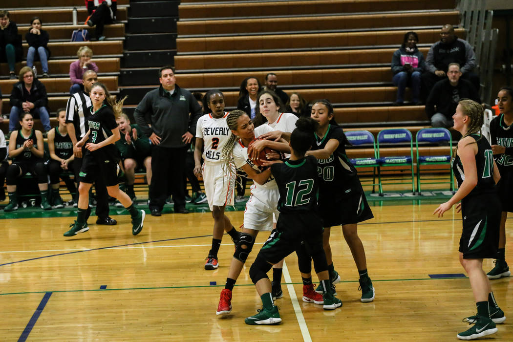 Beverly Hills' Emma Duchemin (23) holds onto the ball as Green Valley's Rian Anderson (12) and Michelle Lagunas-Monroy (20) attempt to steal it during the second quarter of a basketball game durin ...