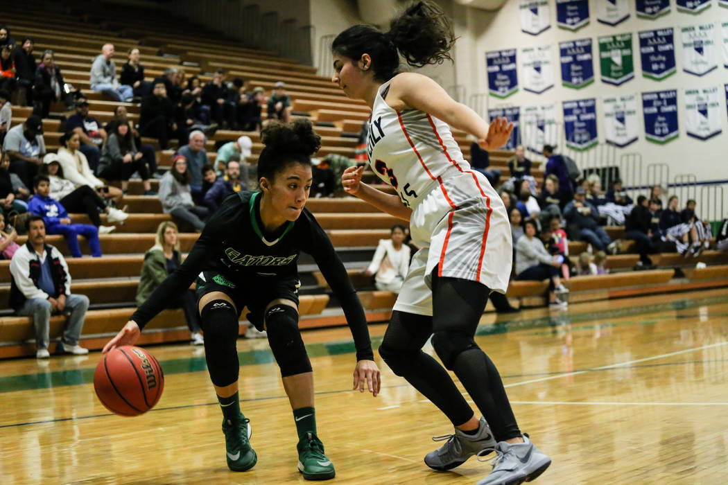 Green Valley's Rian Anderson (12) dribbles the ball past Beverly Hills' Megan Saghian (3) during the fourth quarter of a basketball game during the Gator Winter Classic at Green Valley High School ...