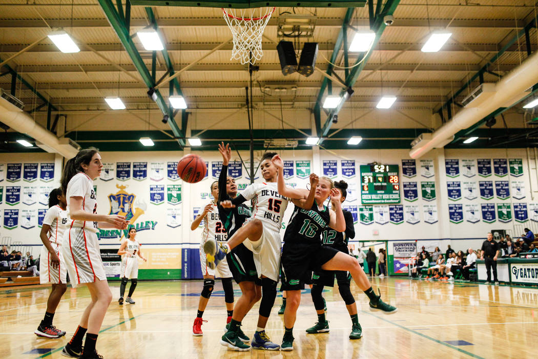 Green Valley's Lusi Soifua (32) and Green Valley's Julia Clark (10) guard Beverly Hills' Michelle Duchemin (15) during the fourth quarter of a basketball game during the Gator Winter Classic at Gr ...