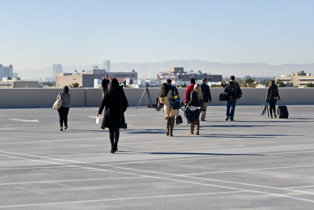 Members of the news media heads toward a staging area at Metropolitan Police Department Headquarters in Las Vegas Wednesday, Dec. 27, 2017, for a press conference about security for the upcoming N ...
