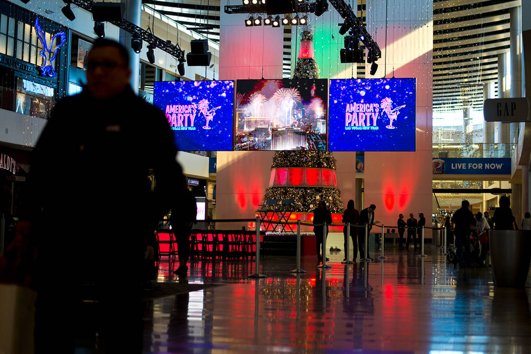 """People walk by during the """"America's Party"""" news conference announcing details of Las Vegas New Year's Eve celebrations inside the Great Hall of the Fashion Show Mall on Thursday, Dec. 21, 2017. D ..."""